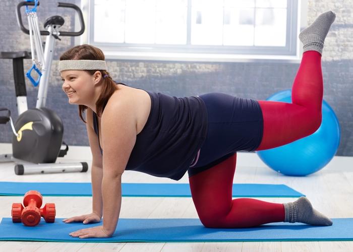 Happy fat woman doing gymnastics